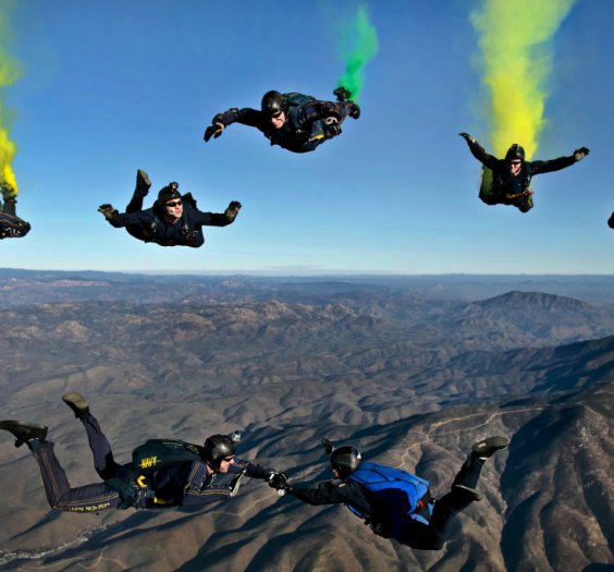 Seven men skydiving above a mountain range. They all wear sunglasses, helmets and full boy suits.